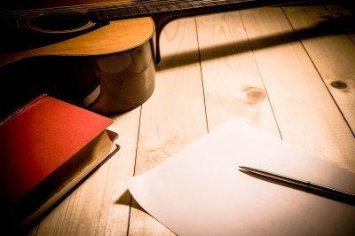 Werktafel met pen papier en gitaar van iemand die geld probeert te verdienen met het schrijven van songteksten